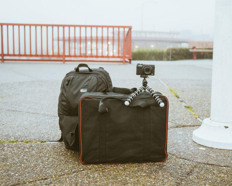 abandoned backpack, suitcase, and camera near bridge