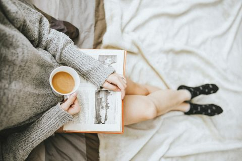 woman reading a book drinking coffee wearing a cozy sweater