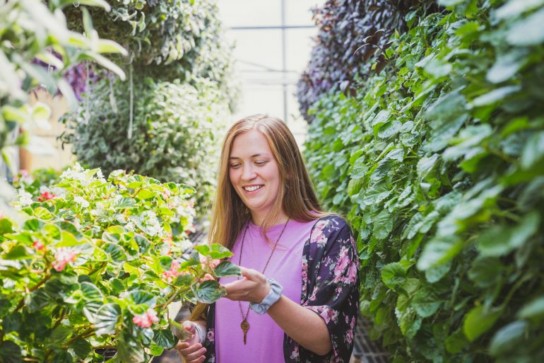 happy young woman smiling in green garden